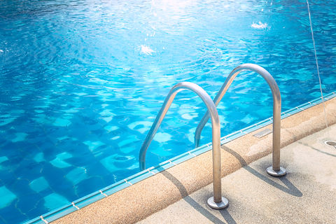 Grab bars ladder in the blue swimming po