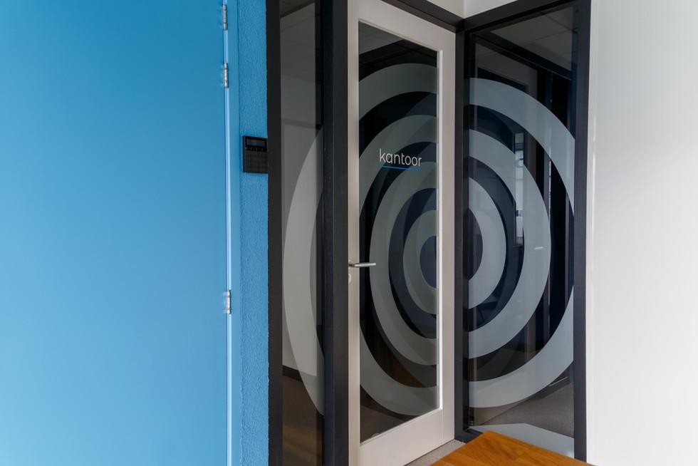 in de entree is de lichtblauwe huiskleur iets minder schreeuwerig toegepast; het totaal oogt fris en verwelkomt. De spiraal in het logo is op de glazen wand en deuren geplaatst; hierdoor is het meteen duidelijk dat het hier geen open doorgang betreft, zonder dat het erg afgesloten is.