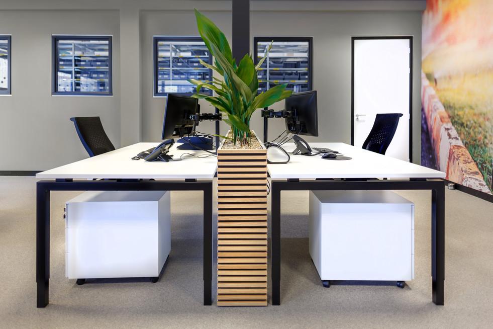 in het interieur ontwerp van het kantoor valt de samenhang tussen alles direct op: de witte vlakken met het zwarte lijnenspel is in zowel de deuren met kozijnen, als in de belijning van de bureaus terug te vinden. De bureaus worden gescheiden door maatwerk kasten met geïntegreerde plantenbak