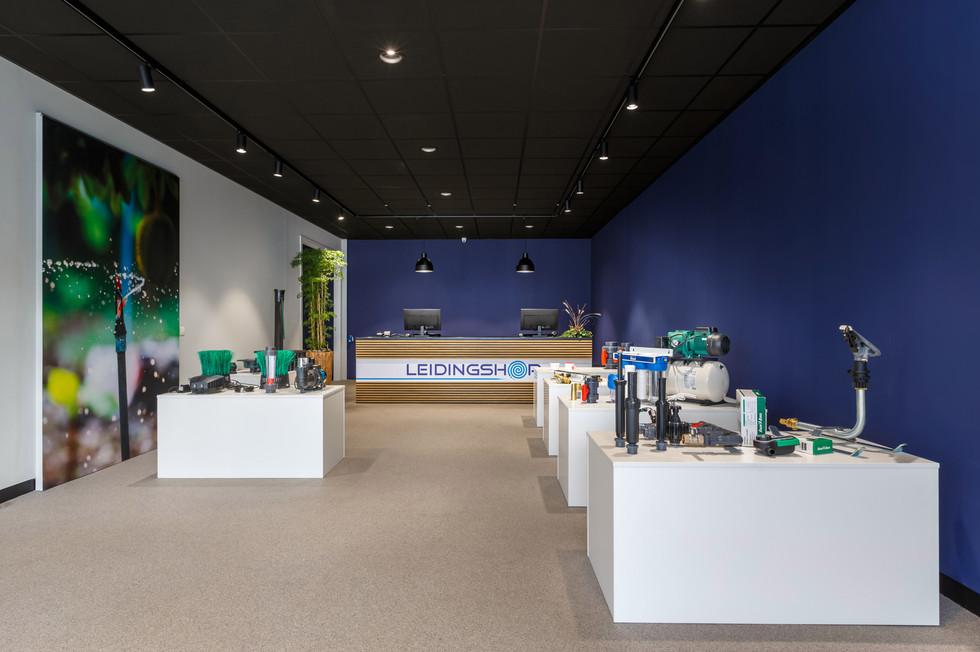 bij dit ontwerp van de showroom staan de producten centraal; deze staan op witte blokken gepresenteerd. De witte blokken steken prachtig af tegen de donkerblauwe wand, welke in de huiskleur van het logo terug te vinden is