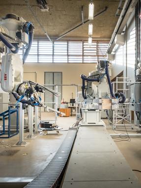 Halle Freyssinet: robot sur track avec pince et robot fixe avec outil de à fil chaud.