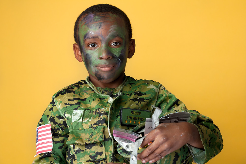 A soldier fresh off the face painting table, he had his candy stashed in his helmet.
