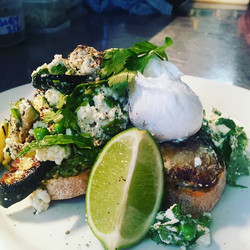 Fresh and tasty, bruschetta with pesto, char grilled zucchini, peas , goat's cheese and a poached eg