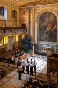 Inside of a church taken from a height. Softly lit. Small choir performs at the front. Christmas tree in the corner.
