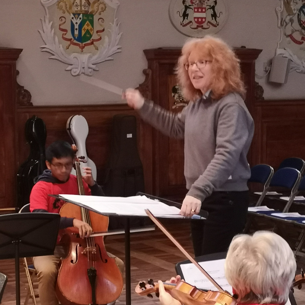 A female conductor in a grey jumper leads the orchestra from the conductors podium