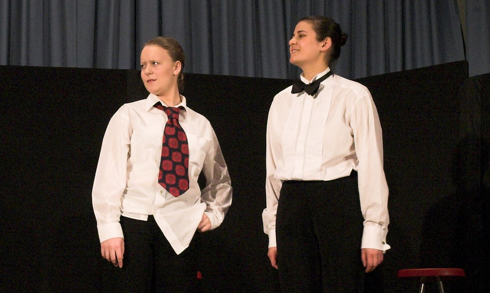 Sarah and another woman on stage in men's shirts and ties. Looking off to the side.