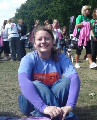 Sarah wearing purple sitting cross legged on the grass, smiling