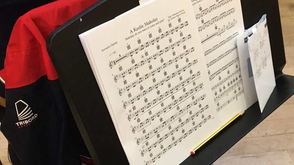 Sheet music for Ghanian folk song 'A Keelie Makolay' rests on a black music stand.