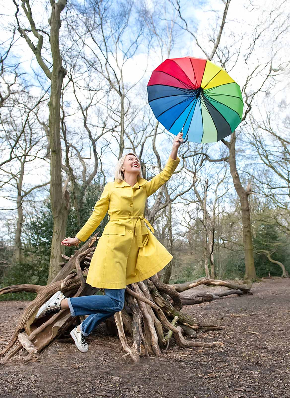 Blonde woman in yellow rain coat, jeans and white shoes. Appears to be floating in the air, holding a rainbow umbrella. Stood in the woods, in front of a homemade den of sticks and logs.