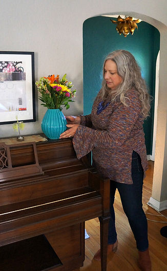 A women with long curly silver hair wearing a multi colored sweater setting an aqua ceramic vase with colorful flowers on the top of an upright piano.