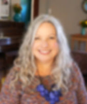 Profile picture of a smiling woman with long curly silver hair wearing a multicolored sweater and blue beaded necklace.