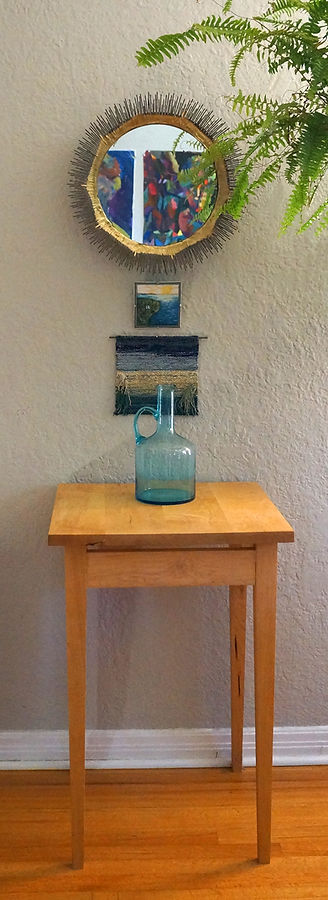 A tall, square maple wood table with aqua colored glass vase setting on it and a small round mirror hanging above it.
