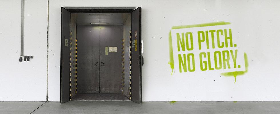 Ein geöffneter schwarzer Aufzug. Rechts daneben ein Schriftzug: NO PITCH. NO GLORY.