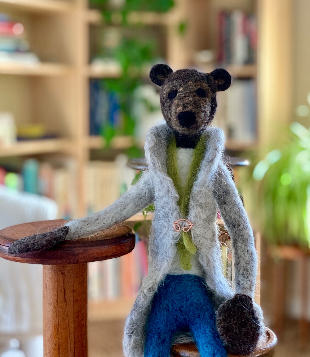 needle felted brown bear named Jessie, sitting on a stool, wearing blue pants, white shirt, gray jacket and sage green scarf