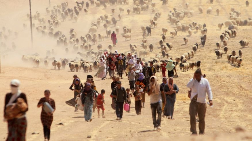 August 10, 2014: Displaced people from the minority Yazidi sect, fleeing violence from forces loyal to the Islamic State in Sinjar town, walk towards the Syrian border, on the outskirts of Mt. Sinjar.  (REUTERS/Rodi Said/File )