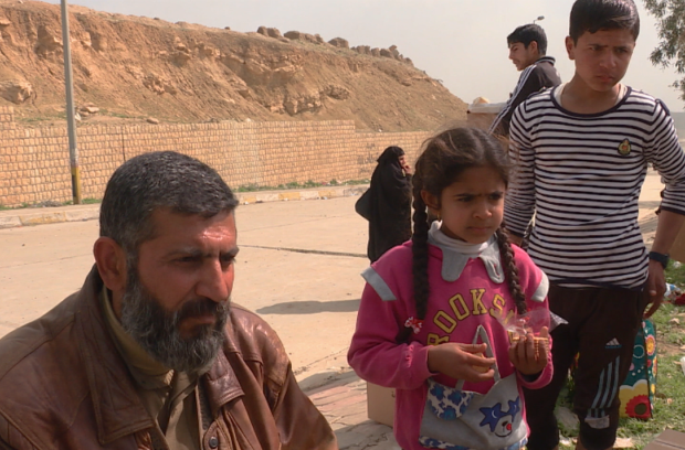 Abu Fahad and his family stopped for some food and sweets after fleeing western Mosul on Sunday. (Glen Kugelstadt/CBC)