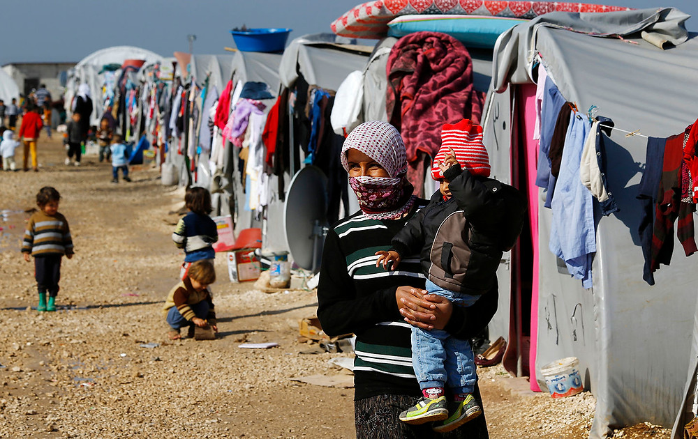 A Kurdish refugee woman from the Syrian town of Kobani walks with her baby at a refugee camp in the border town of Suruc, Sanliurfa province, February 1, 2015. (Reuters / Umit Bektas)
