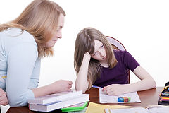A woman helps his child in homework.jpg