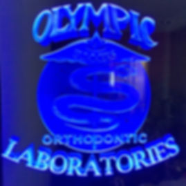 An Ortodontic Laboratory, Olympic Laboratories Logo etched in glass and lit up.