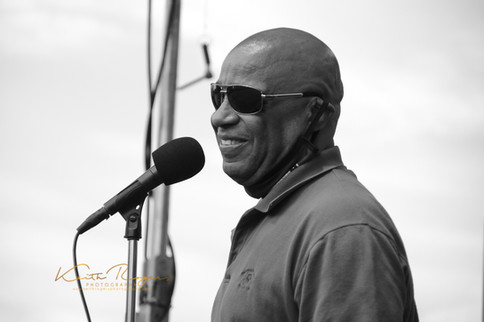 Frank Senior smiling at the microphone. Black and white photo.