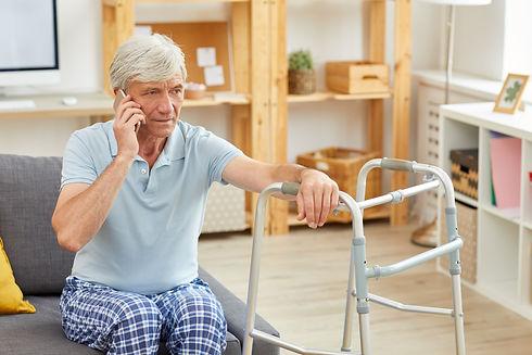Senior man with grey hair sitting on sof