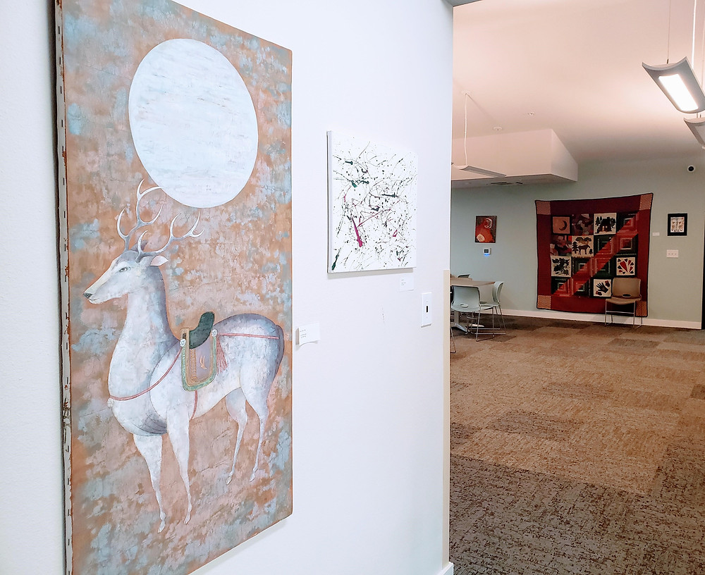 Artwork on the walls of a common area. Foreground: a large painting of a stag under a full moon, next to a smaller splatter painting. Background: a large quilt flanked by smaller drawings and paintings.