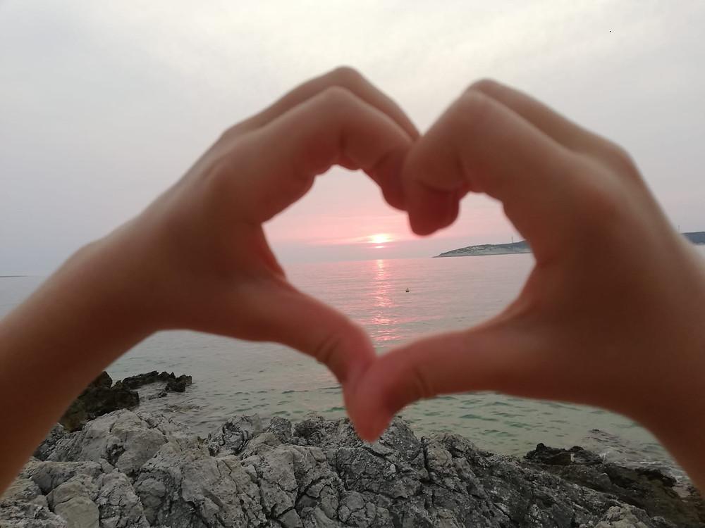 Herzform aus Händen vor Sonnenuntergang am Meer