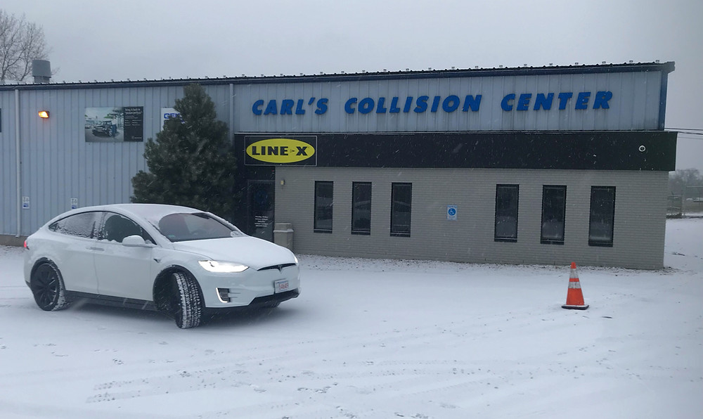 Tesla in front of Carl's Collision Center
