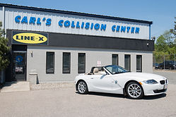 White BMW convertible infront of Carl's Collision Center
