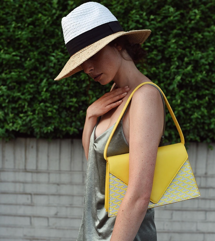 interview with pop sustainable accessories, girl wearing olive dress, straw hat and yellow monogram handbag