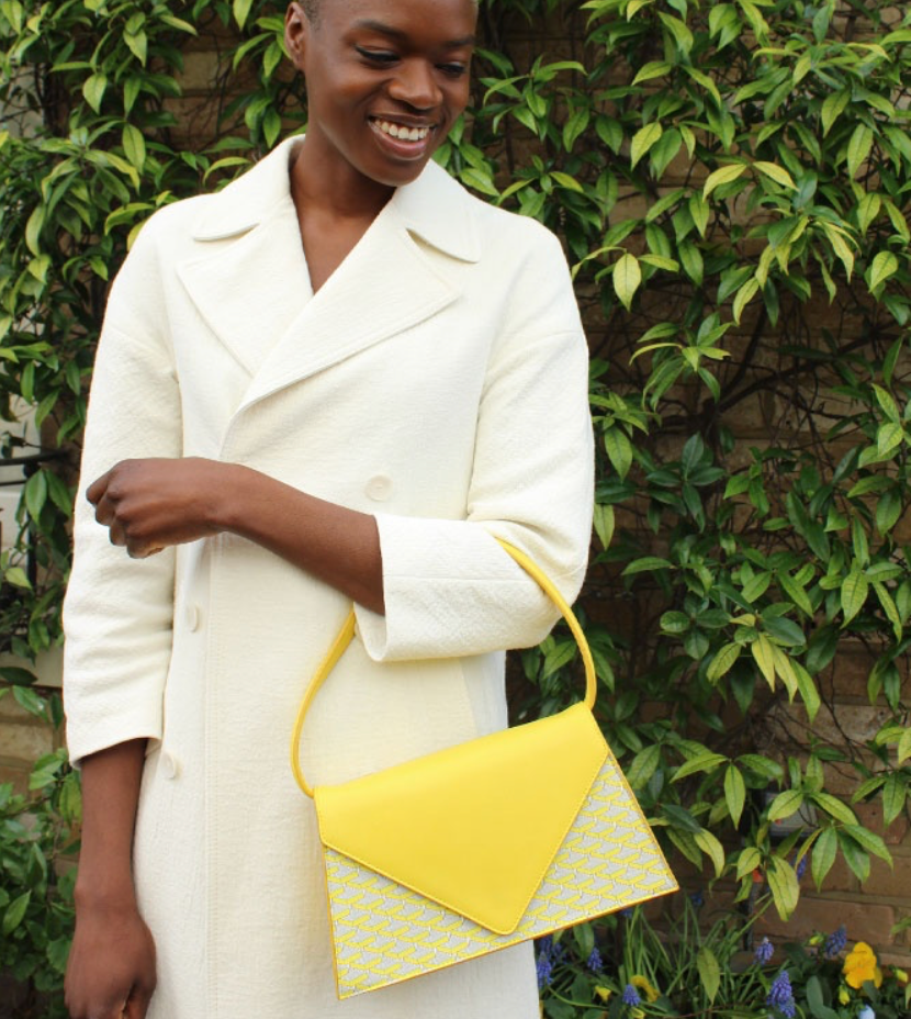 interview with pop sustainable accessories, black woman wearing white trench coat and yellow monogram hand bag