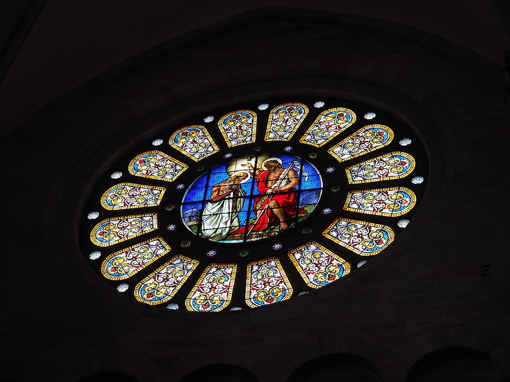 A rose-window reminiscent of a wheel, with Jesus at the center.