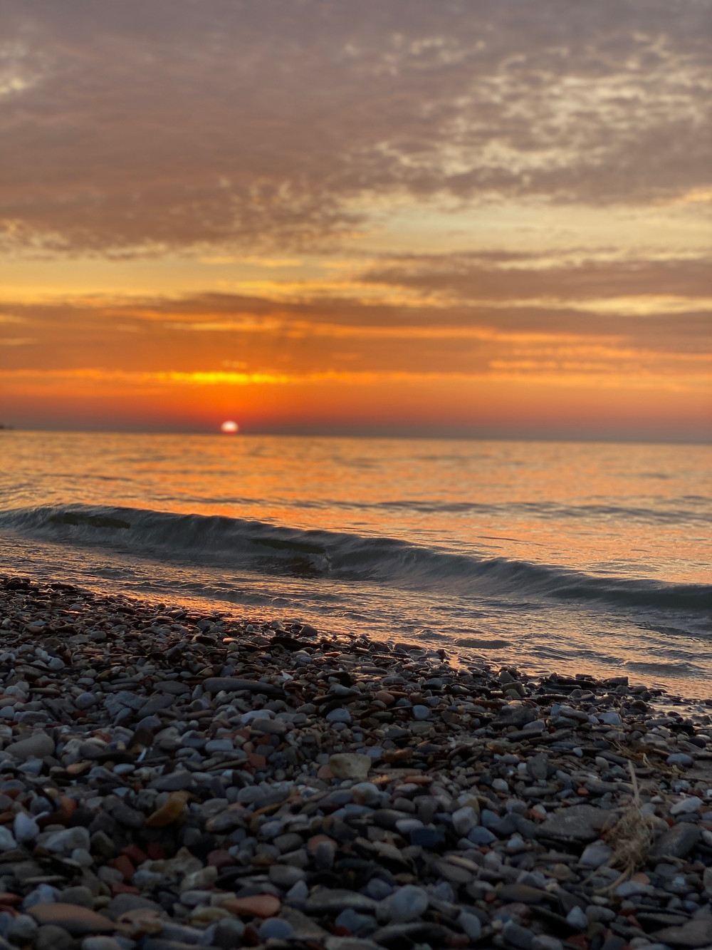 A beautiful orange sunset over ipperwash beach, stones and water.