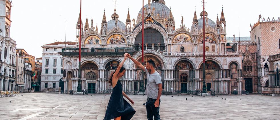 Canva - Couple dances in basilica plaza.
