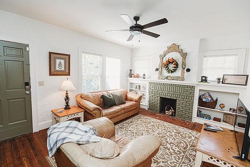 boho-living-room-green-brick-fireplace-leather-sofa-birmingham-alabama-vacation-rental