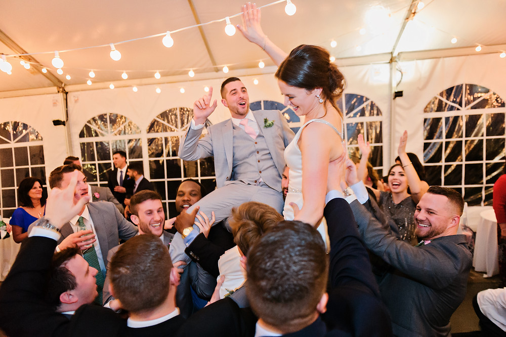 Wedding guests lifting up bride and groom