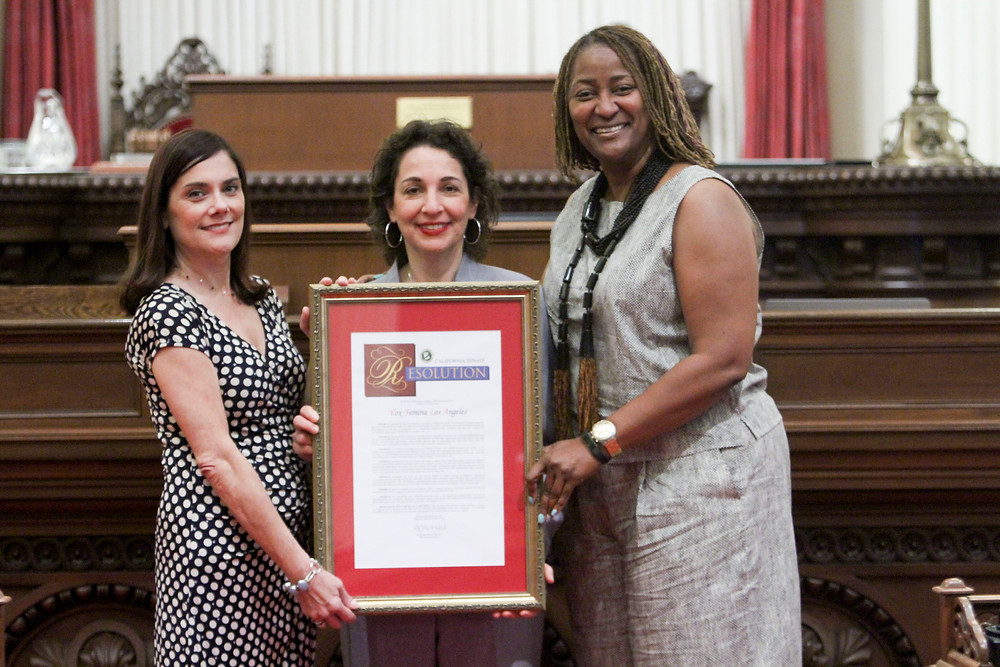 Executive Director Rebecca Wink (left) and Artistic Director Iris Levine (center) accept the award from Senator Holly Mitchell.