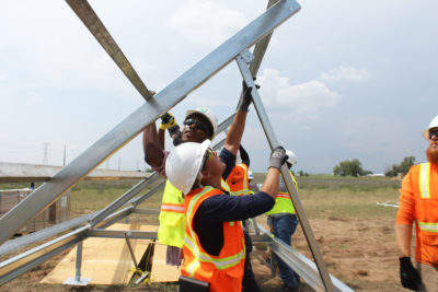 📷 Workers receive job training while building a shared solar farm in Platteville, Colorado. COURTESY OF GRID ALTERNATIVES.