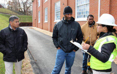 📷 Solar contractor Brad Boston (center) and utility representatives meet with engineer Pranay Kohli to discuss a community solar project at DuPont Park Seventh Day Adventist Church in Washington, D.C. COURTESY OF GROUNDSWELL