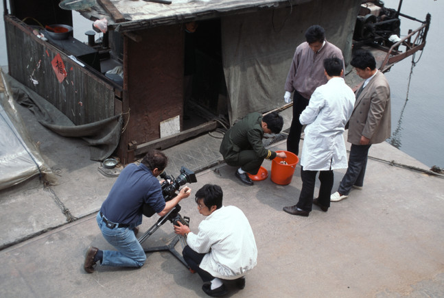 Inspecting a severed head, found floating in Suzhou Creek