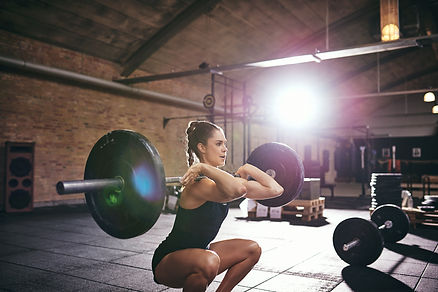 strong-woman-pumping-heavy-barbell-at-gy