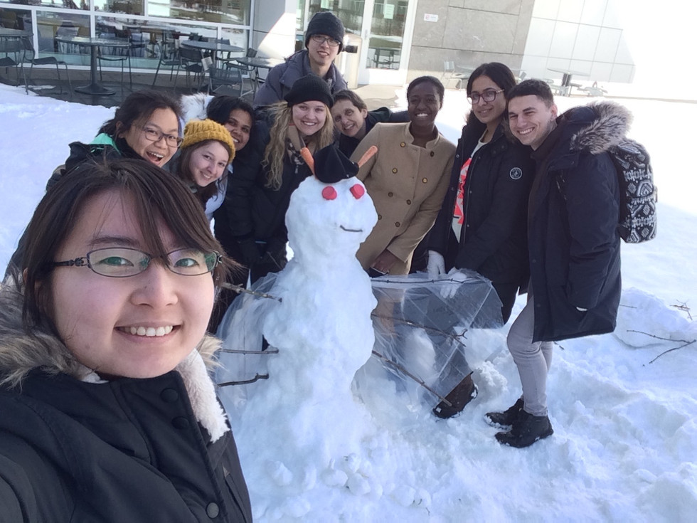 Wolfner lab group photo in winter 2016-2017. Ten lab members pose in front of a snow fly they built next to the Biotechnology Building.