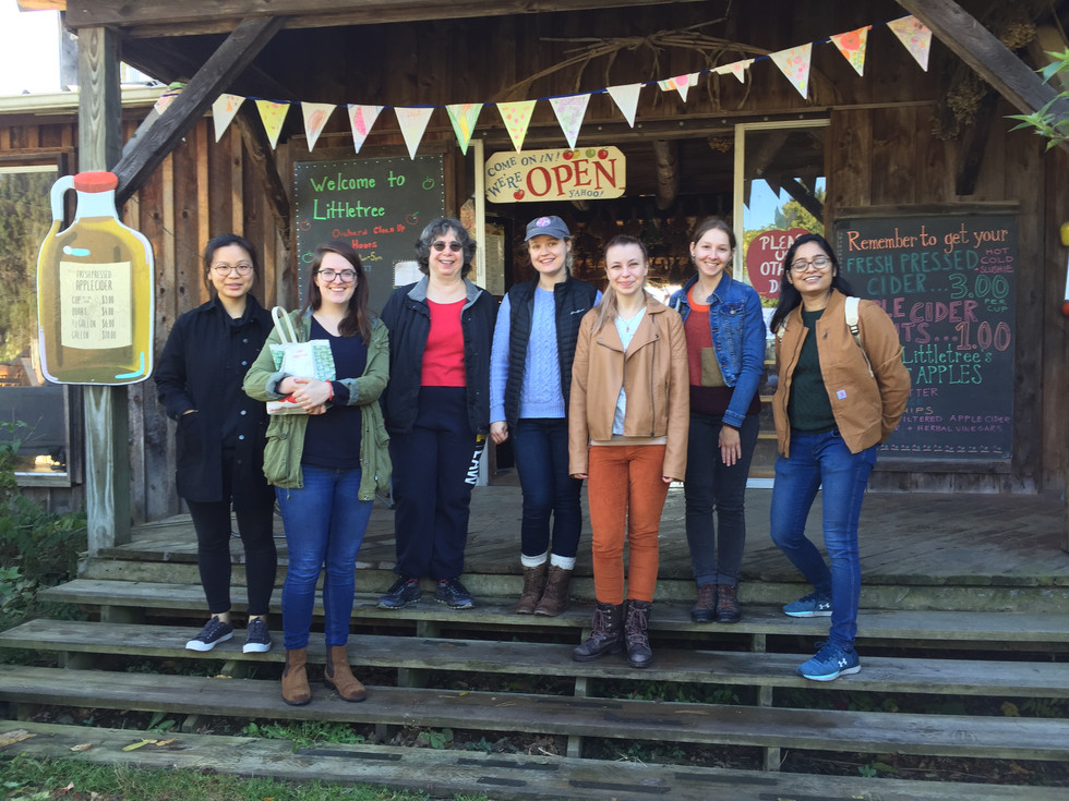 Wolfner lab member go apple picking in an orchard near Ithaca. Seven lab members stand in front of the farm stand at the orchard.