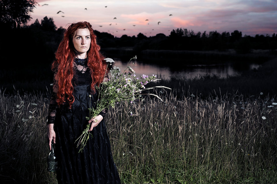 photo of lady next to a river dressed in black holding some dead flowers