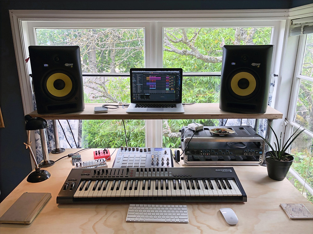 Desk top with a computer and various music equipment.