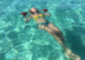 Chica nadando con estrellas de mar en Ibiza