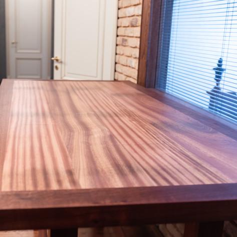 Выполнен полностью из разных распилов массива древесины сапеле.  Эта порода имеет кедровый запах, яркий рисунок средней текстуры и красно-коричневый цвет с золотистым блеском. По классу прочности соответствует дубу. Длина столешницы 1800 мм. Ширина 900 мм. Толщина столешницы 50 мм. Стоимость  140 000 руб. Мы можем выполнить стол из других пород деревесины по эскизу заказчика или дизайнера. Стол может быть дополнен ящиками или тумбами. Ориентировочный срок изготовления 2 мес.