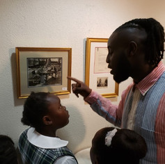 Collector Israel Johnson explaining a photograph of the Duke of Windsor to young students