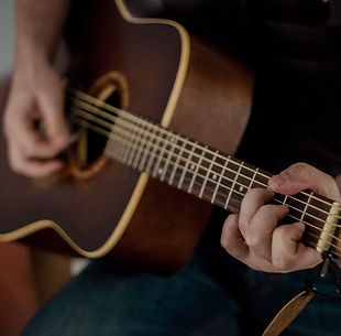 person-playing-brown-guitar-1407322-min_