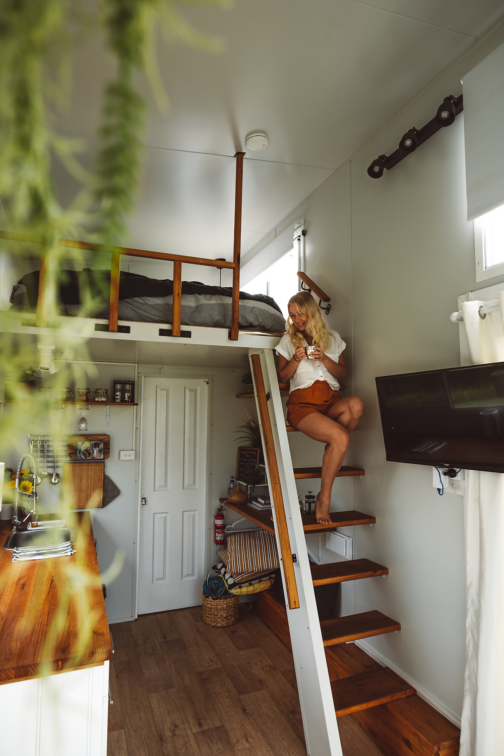 Interior of a tiny home showing inside of kitchen and bedroom in Australia